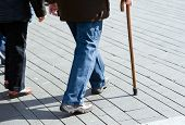 stock photo of rollator  - An elderly man walking on the street with his walking stick - JPG