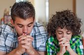 stock photo of kneeling  - Two Hispanic brothers praying and having their daily Christian devotional at home - JPG