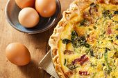 stock photo of bacon  - Homemade Spinach and Bacon Egg Quiche in a pie crust - JPG