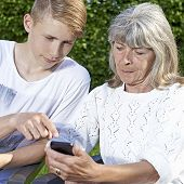 Teen and senior with smartphone