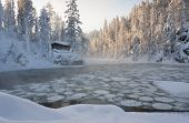 foto of laplander  - Small hut or log caping at the cliff edge near icy pond in white snowy forest in winter in Lapland Finland - JPG