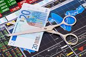 Scissors Cutting  Euro  Banknote. Financial Charts And Columns Of Prices As Background. Selective Fo