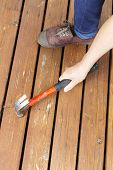 Female Hand Adjusting Wooden Cedar Boards On Outdoor Deck