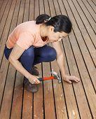 Mature Woman Adjusting Boards On Wooden Cedar Deck