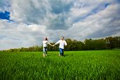 Happy Couple Running On A Grass