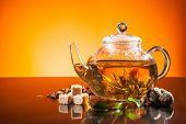 Teapot with blooming tea on glass