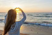 stock photo of peace-sign  - Blonde young girl holding hands in heart shape framing setting sun at sunset on ocean beach - JPG