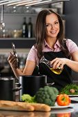 Smiling young woman adding oil to pot on a modern kitchen