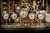 stock photo of analog clock  - Vintage clocks on a bar counter in a pub - JPG