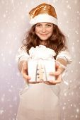 Santa girl offers gift box, cute teenager wearing shiny hat isolated on pink snowing background, Christmastime surprise