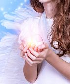 Closeup on little angel holding in hands candle, body part of teen girl wearing white dress and big fluffy wings, Christmas celebration, religious holiday concept