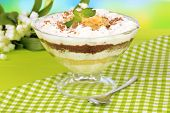 Delicious dessert with banana and caramel on table on bright background