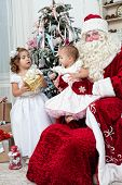 foto of saint-nicolas  - Saint Nicolas gives to small children Christmas gifts - JPG