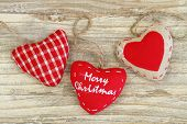Merry Christmas on canvas hearts on wooden surface