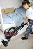 Kid using vacuum cleaner in his room