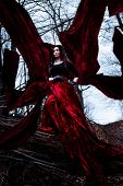 Mysterious woman or witch in long red dress standing in dark forest with flying fabric