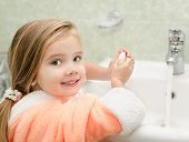 Smiling Little Girl Washing Hands In Bathroom
