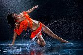 stock photo of dancing rain  - Woman dancing under rain in orange dress - JPG