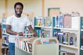 Portrait of African American librarian with trolley of books in bookstore