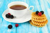 Cup of tea with cookies and berries on table close-up