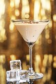 foto of bailey  - Baileys liqueur in glass on golden background - JPG
