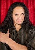 stock photo of raunchy  - Attractive Latino man with long hair and eyeliner - JPG