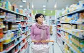 Woman Pushing Shopping Cart Looking At Goods In Supermarket