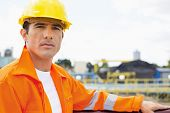 Portrait of handsome mid adult man wearing protective workwear at construction site