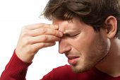 stock photo of upset  - Man holding his nose because of a sinus pain - JPG