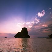 Sunset At Tropical Beach Landscape. Ocean Coast With Rock Formation Island Silhouette Under Evening