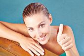 Happy smiling woman in water of swimming pool holding her thumbs up