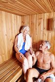 Happy senior couple sitting together in sauna of a hotel