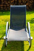 Relax. Empty Deck Chair On Grass In Garden.