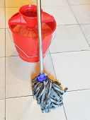 Red Bucket With Foamy Water And Mopping The Floor