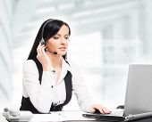 Young, confident and beautiful customer support operator working in a call center
