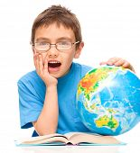 Little boy is holding his face in astonishment while sitting at table with globe, isolated over whit