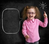 stock photo of infant  - Happy kid girl in glasses with bright idea standing near school blackboard in classroom - JPG