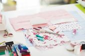 Closeup On Table Of Seamstress With Scissors Threads And Fabric