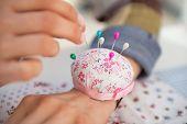 Closeup On Seamstress Putting Needle In Pincushion