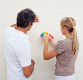 Couple Choosing A Color To Paint A Room