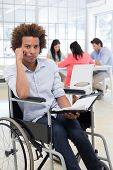 Stern businessman in wheelchair holds planner and frowns at camera in the office