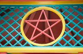 stock photo of wiccan  - A red star of China among a colorful lattice work - JPG