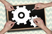Composite image of multiple hands drawing cogs with chalk against blackboard