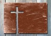 Vintage old grungy paper banner with a Christian religious cross over ancient wood background