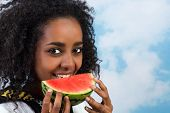 Pretty African Ethiopian girl eating a juicy watermelon