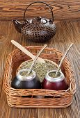 foto of calabash  - Yerba mate and mate in calabash on a wicker tray on a wooden background - JPG