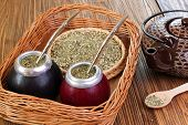 stock photo of calabash  - Yerba mate and mate in calabash on a wicker tray on a wooden background - JPG
