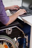 Man On Wheelchair Working On Laptop