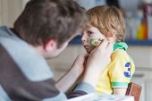 Father Painting Flag On Face Of Little Son