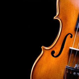 image of musical instrument string  - a beautiful vintage violin over dark background - JPG